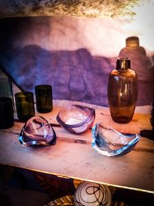 Farbige Glasschalen und Gefäße auf einem Holzstand in blau und violett.